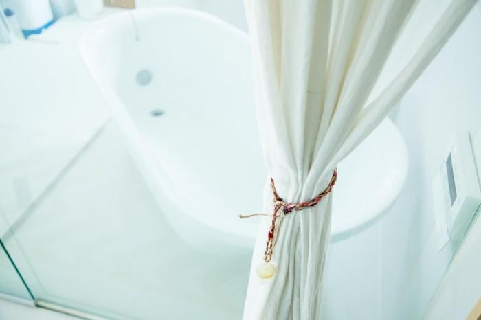 スペイン製のバスタブ。バスルームはガラス張りで、廊下とキッチンが眺められる。