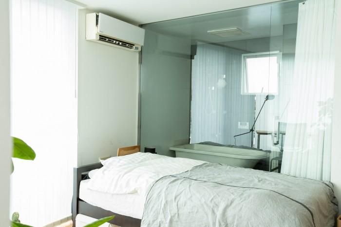 ベッドとお風呂がガラスで仕切られている。まるでバスルーム、という絵の様でもある。